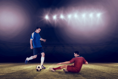 Football players tackling for the ball against football pitch under spotlights Stock Photo - 29046882