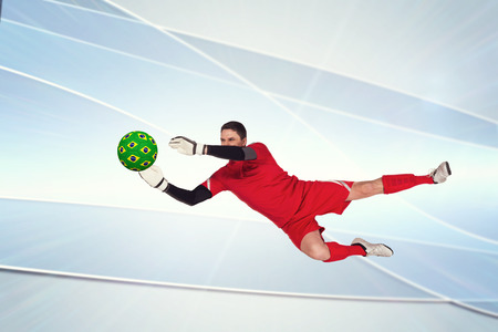 goal keeper: Fit goal keeper jumping up against linear grey background Stock Photo