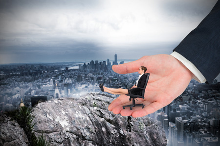 Businesswoman sitting on swivel chair with feet up in large hand against large rock overlooking huge city photo