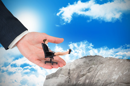 Businesswoman sitting on swivel chair with feet up in large hand against large rock overlooking blue sky photo