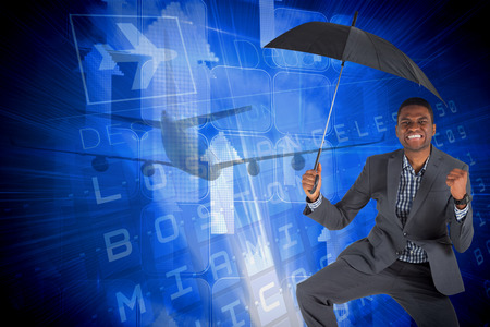 Businessman cheering and holding umbrella against blue departures board for american cities photo