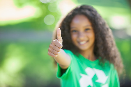 activist: Young environmental activist smiling at the camera showing thumbs up on a sunny day