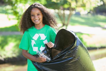 ni�os reciclando: Joven activista ambiental sonriendo a la c�mara recogiendo basura en un d�a soleado