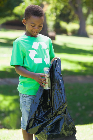 Young boy in recycling tshirt picking up trash on a sunny day photo