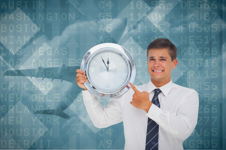 Anxious businessman holding and showing a clock against airport departures board for america photo