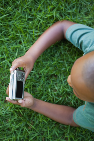 Little boy lying on grass looking at digital camera on a sunny day photo