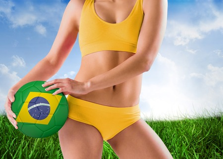 Fit girl in yellow bikini holding brazil football against field of grass under blue sky photo