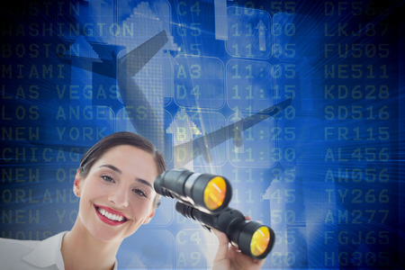 Smiling business woman with binoculars against airport departures board for america photo