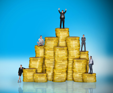 Composite image of business people on pile of coins against blue background with vignette Stock Photo