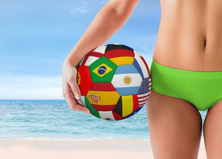 Fit girl in green bikini holding flag football against beach scene photo