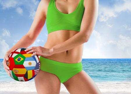 Fit girl in green bikini holding flag ball against beach scene photo