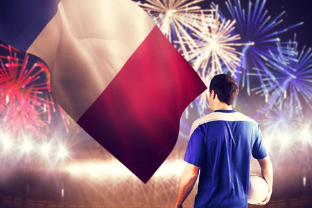 Handsome french football player holding the ball against fireworks exploding over football stadium photo