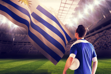 Handsome football player in blue jersey against football stadium photo