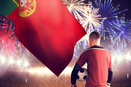 Goalkeeper in red holding the ball against fireworks exploding over football stadium photo