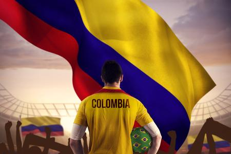 bandera de colombia: Retire contra gran estadio de fútbol bajo el cielo azul nublado