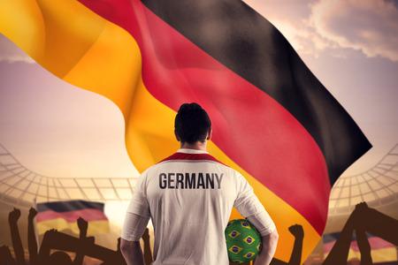 Deutschland Fußball-Spieler mit Ball gegen große Fußballstadion unter strahlend blauem Himmel