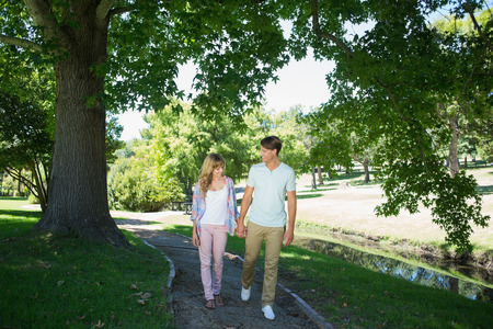 Cute affectionate couple walking hand in hand in the park on a sunny day photo