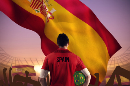 Spain football player holding ball against large football stadium under purple sky photo