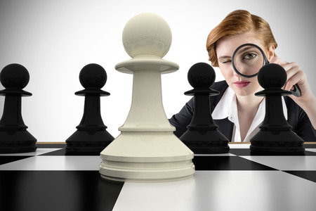 Composite image of focused businesswoman with magnifying glasses with chessboard photo