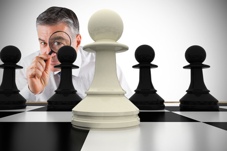 Composite image of focused businessman with magnifying glasses with chessboard Stock Photo - 29046638