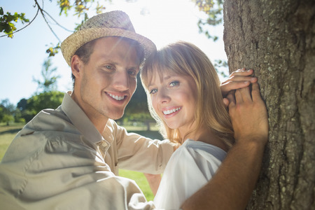 Cute couple leaning against tree in the park smiling at camera on a sunny day photo