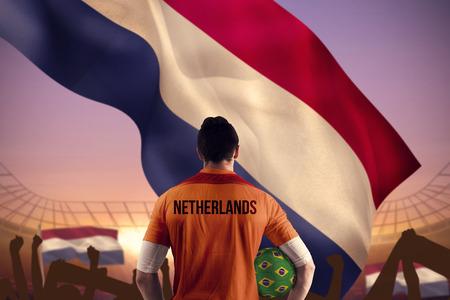 Netherlands football player holding ball against large football stadium under purple sky photo