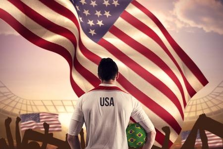 world championships: Usa football player holding ball against large football stadium under bright blue sky