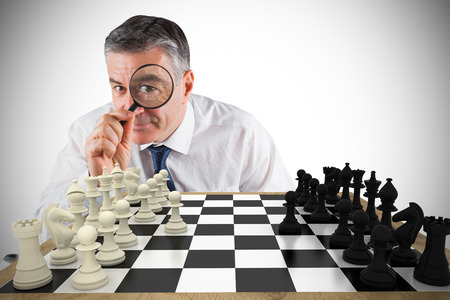 Composite image of focused businessman with magnifying glass with chessboard Stock Photo - 29046619
