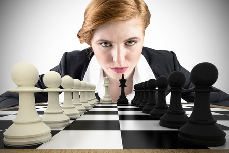 focused: Composite image of focused businesswoman with chessboard