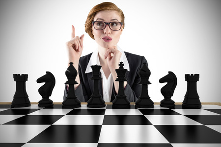 pawn adult: Composite image of thinking redhead businesswoman with chessboard Stock Photo