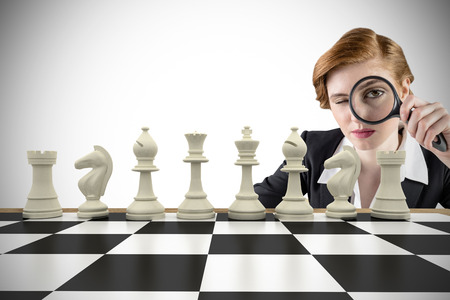 Composite image of focused businesswoman with magnifying glass with chessboard Stock Photo - 29046621