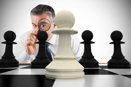 Composite image of focused businessman with magnifying glass with chessboard Stock Photo - 29048704