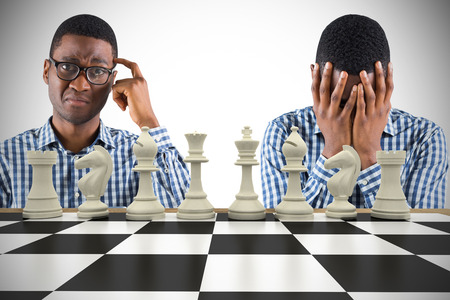 pawn adult: Young businessman with head in hands with chessboard against white background with vignette