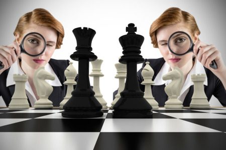 Focused businesswoman with magnifying glass with chessboard against white background with vignette Stock Photo - 29048711