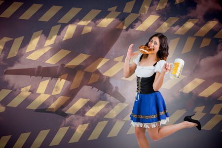 Pretty oktoberfest girl holding beer tankard and pretzel against cloudy sky photo