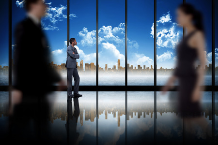 Business people walking in a blur against room with large window looking on city skyline photo