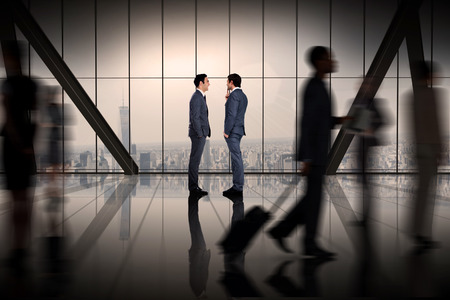 Businessmen talking against room with large window looking on city photo