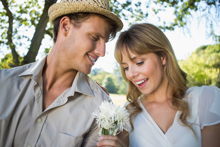 Smiling man offering his girlfriend a white flower in the park on a sunny day photo
