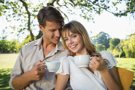 Smiling couple having tea outside in a cafe on a sunny day photo