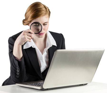 Redhead businesswoman using her laptop on white background photo