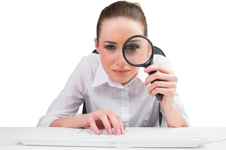 Businesswoman typing and looking through magnifying glass on white background Stock Photo - 29046512
