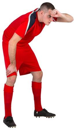 bending over: Tired football player bending over on white background Stock Photo