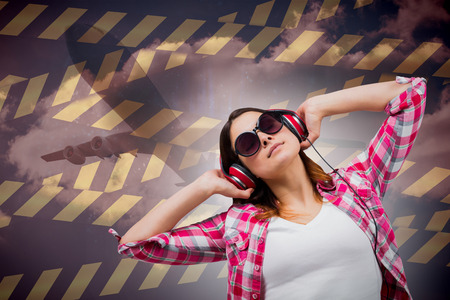 Casual brunette listening to music against cloudy sky photo