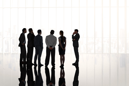businessman standing: Composite image of business colleagues standing in large room overlooking city