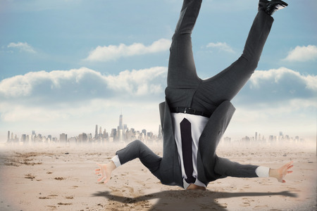 burying: Businessman burying his head against cityscape on the horizon Stock Photo