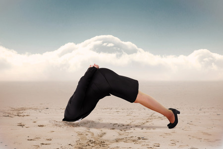 burying: Businesswoman burying her head against cloudy sky background