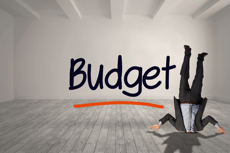 burying: Businessman burying his head against budget written in bright room Stock Photo