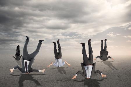 Businessmen burying their heads against desert landscape