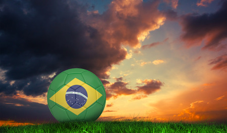 Football in brasil colours against green grass under dark blue and orange sky photo