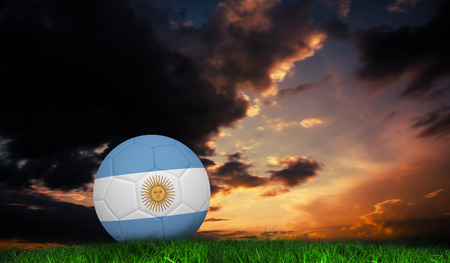 Football in argentina colours against green grass under dark blue and orange sky photo